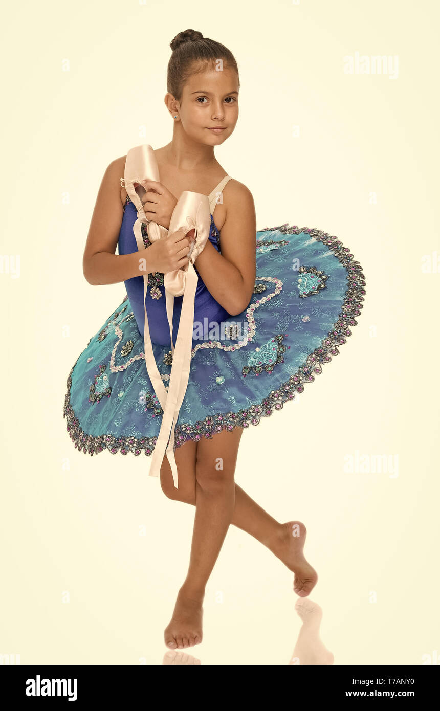 Exercises to develop pointe shoes dance skill. Child happy holds ballet shoes important attribute excellent ballerina. Girl ballerina holds pointe shoes in hand white background. Professional advice. - Stock Image