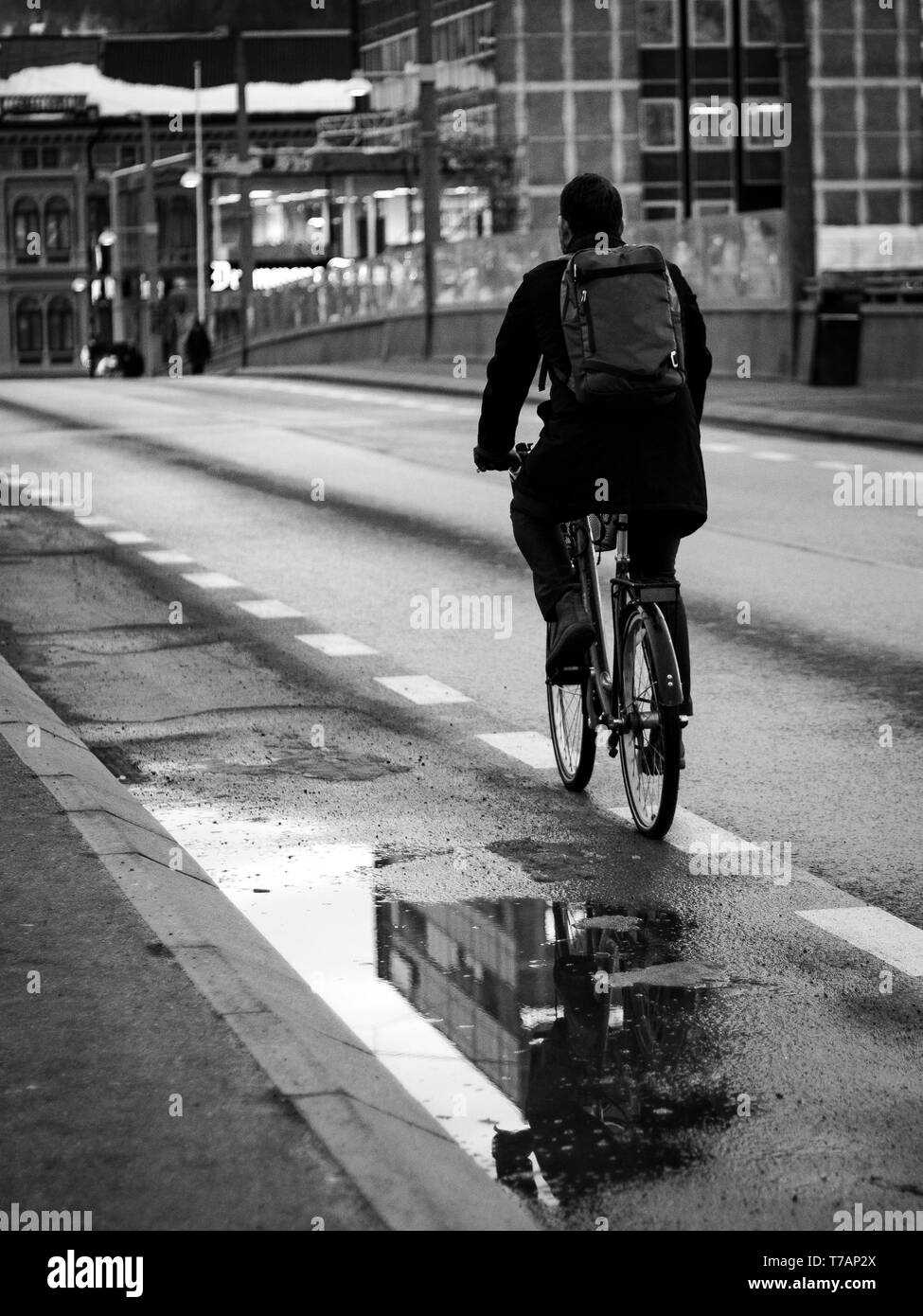 Man riding his bike in the city. Water pit reflecting buildings - Stock Image