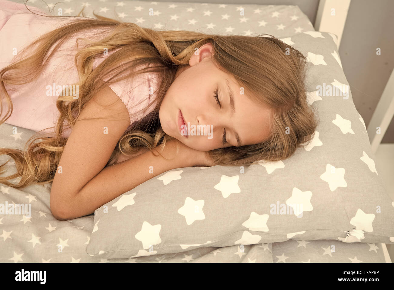Sweet dreams. Girl child long hair fall asleep close up. Quality of sleep depends on many factors. Choose proper pillow to sleep well. Girl on little pillow bedclothes background. Sleeping beauty. - Stock Image