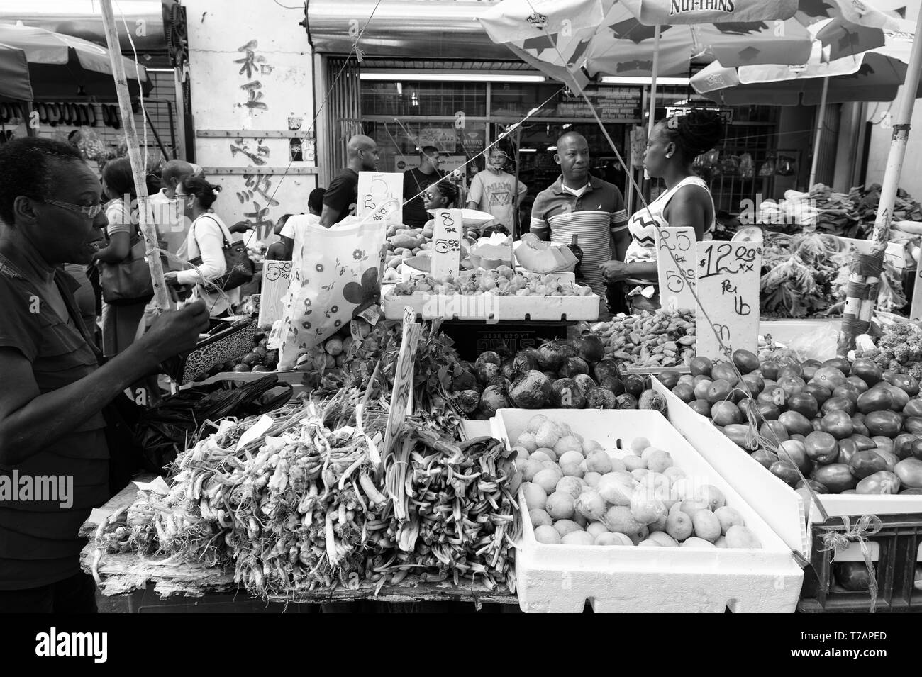 Port of spain, Trinidad and Tobago - November 28, 2015: fresh vegetables and fruit displayed for sale on local south market outdoors on streetscape background - Stock Image