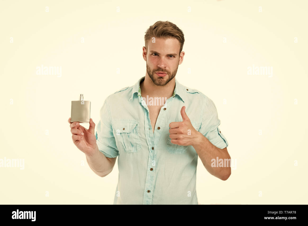 Man confident face recommend perfume shows thumb up gesture. Guy with bristle bottle perfume he likes this fragrance. Male fragrance concept. Man handsome recommend pleasant aroma for male. - Stock Image