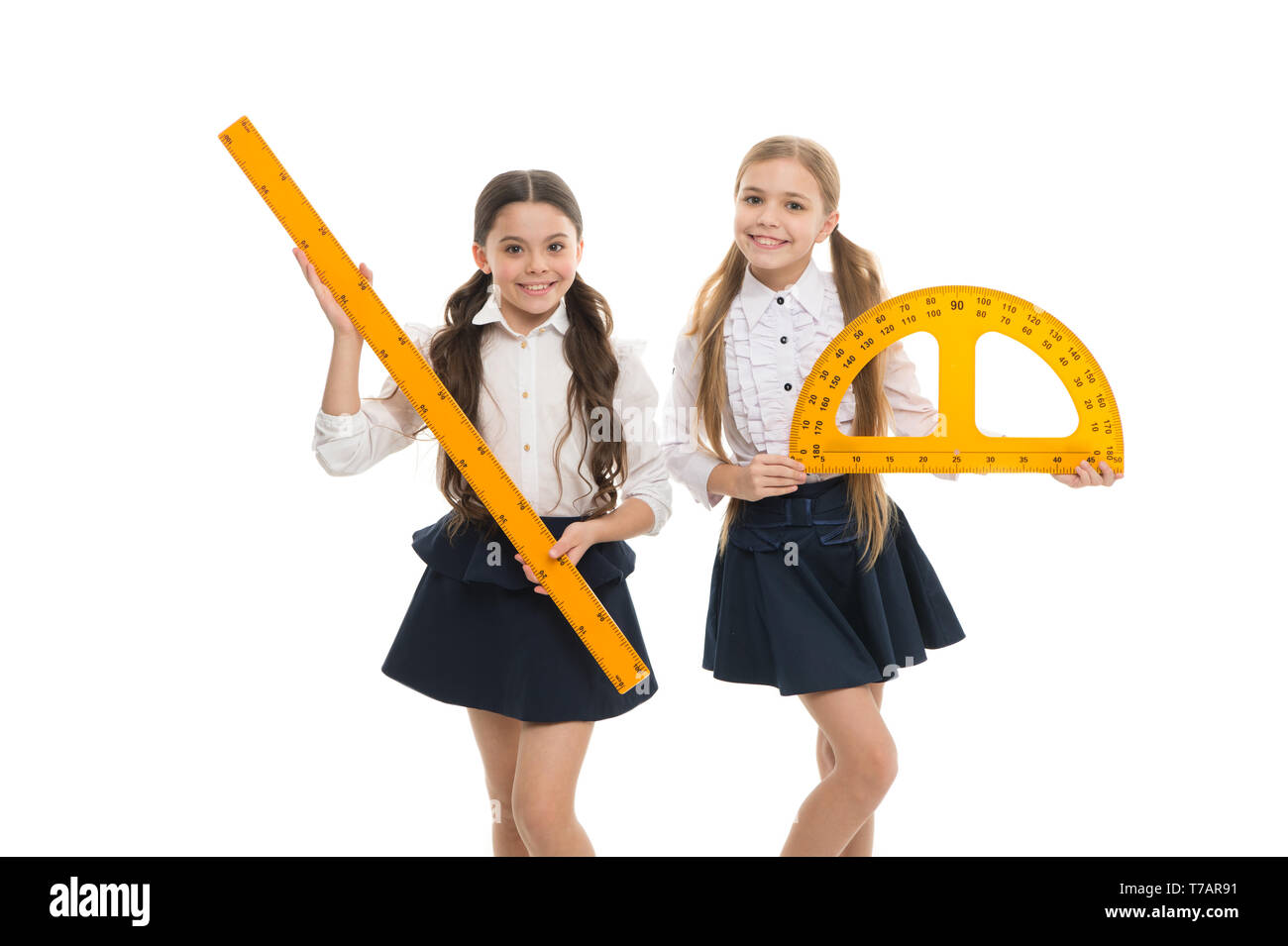Pupils cute girls with big rulers. Favorite school subject. Education and school concept. School students learning geometry. Kids school uniform isolated white. STEM concept. Draw geometric figures. - Stock Image