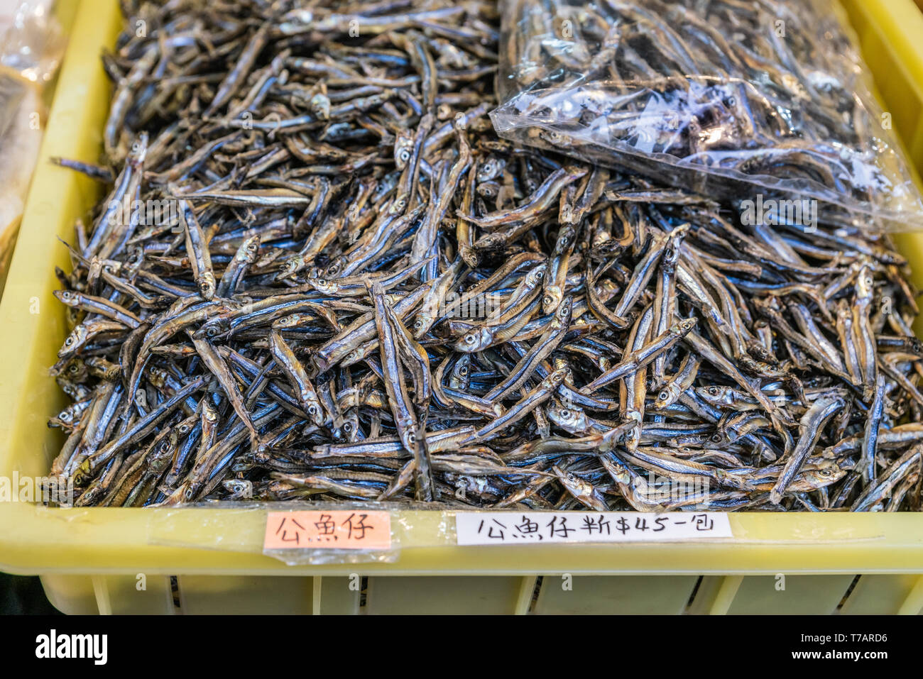 Hong Kong, China - March 7, 2019: Tai O Fishing village. Closeup of Yellow basis filled to the top with brown-blue-yellow dried ansjovis. - Stock Image
