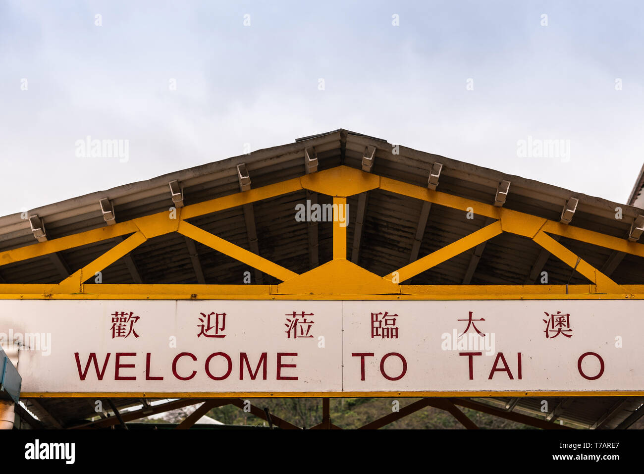 Hong Kong, China - March 7, 2019: Tai O Fishing village. Dual lingual red-on-white yellow sign welcoming visitors to the village, under yellow-beamed  - Stock Image