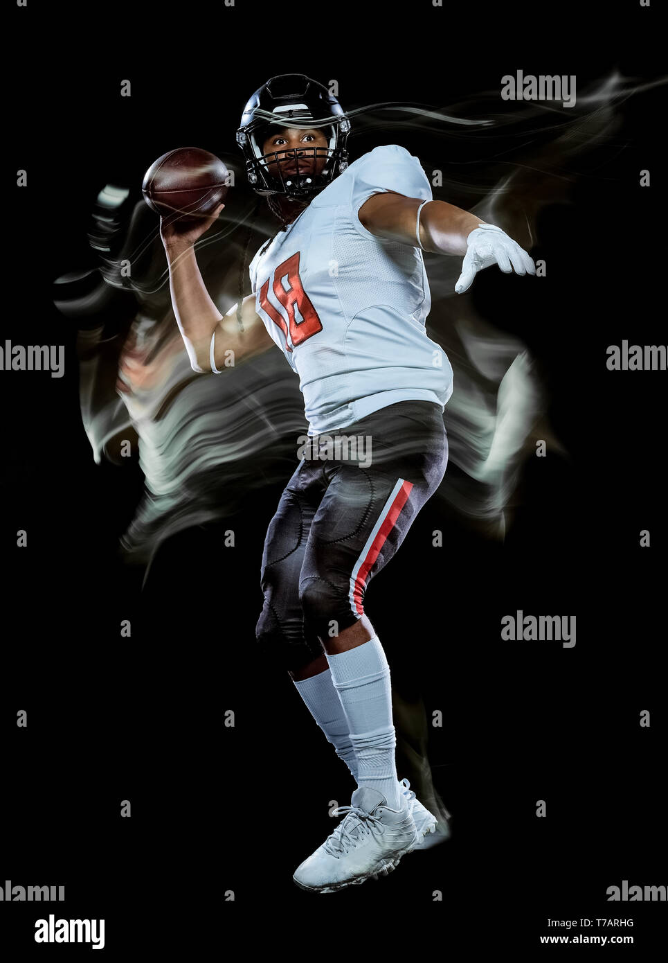 one african american football player man studio shot isolated on black background with light painting with blurred motion speed effect - Stock Image