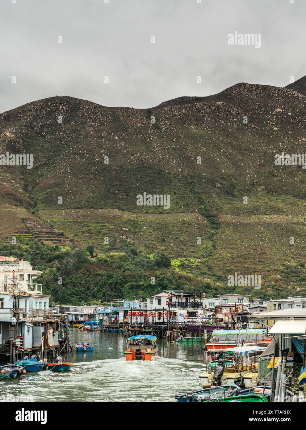 Hong Kong, China - March 7, 2019: Tai O Fishing village. Portrait, Motor sloop for tourists sails on river flanked on both sides by buildings. Green h - Stock Image