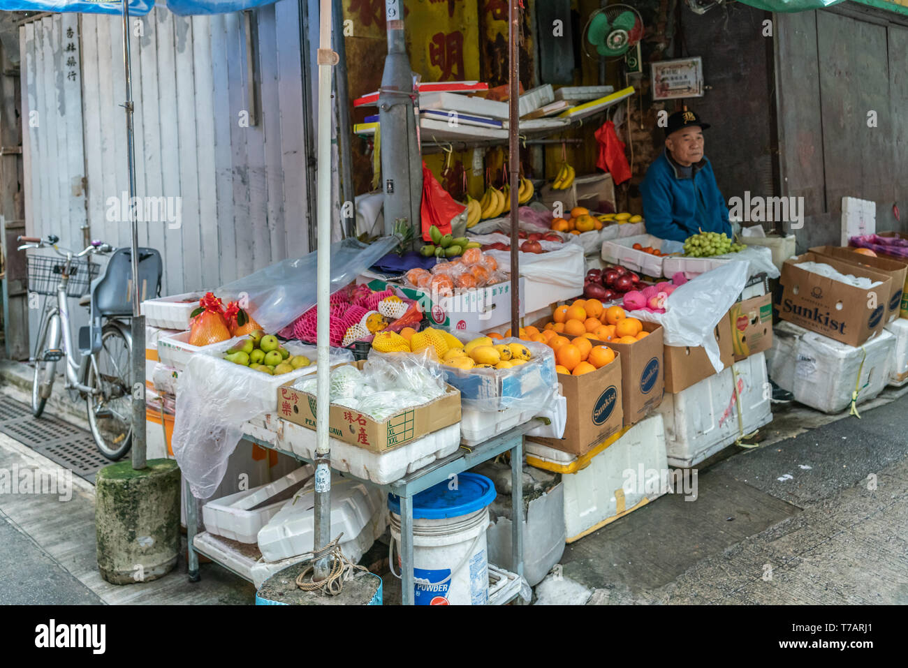 Hong Kong, China - March 7, 2019: Tai O Fishing village. Fruit booth with rich choice on corner of street. Older male vendor in blue vest. Colors by t - Stock Image