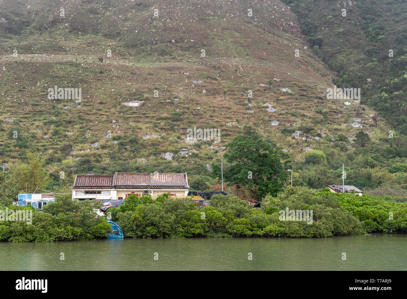 Hong Kong, China - March 7, 2019: Tai O Fishing village. Cemetery on flank of green hill has Chinese style family monuments. Front is river and house  - Stock Image