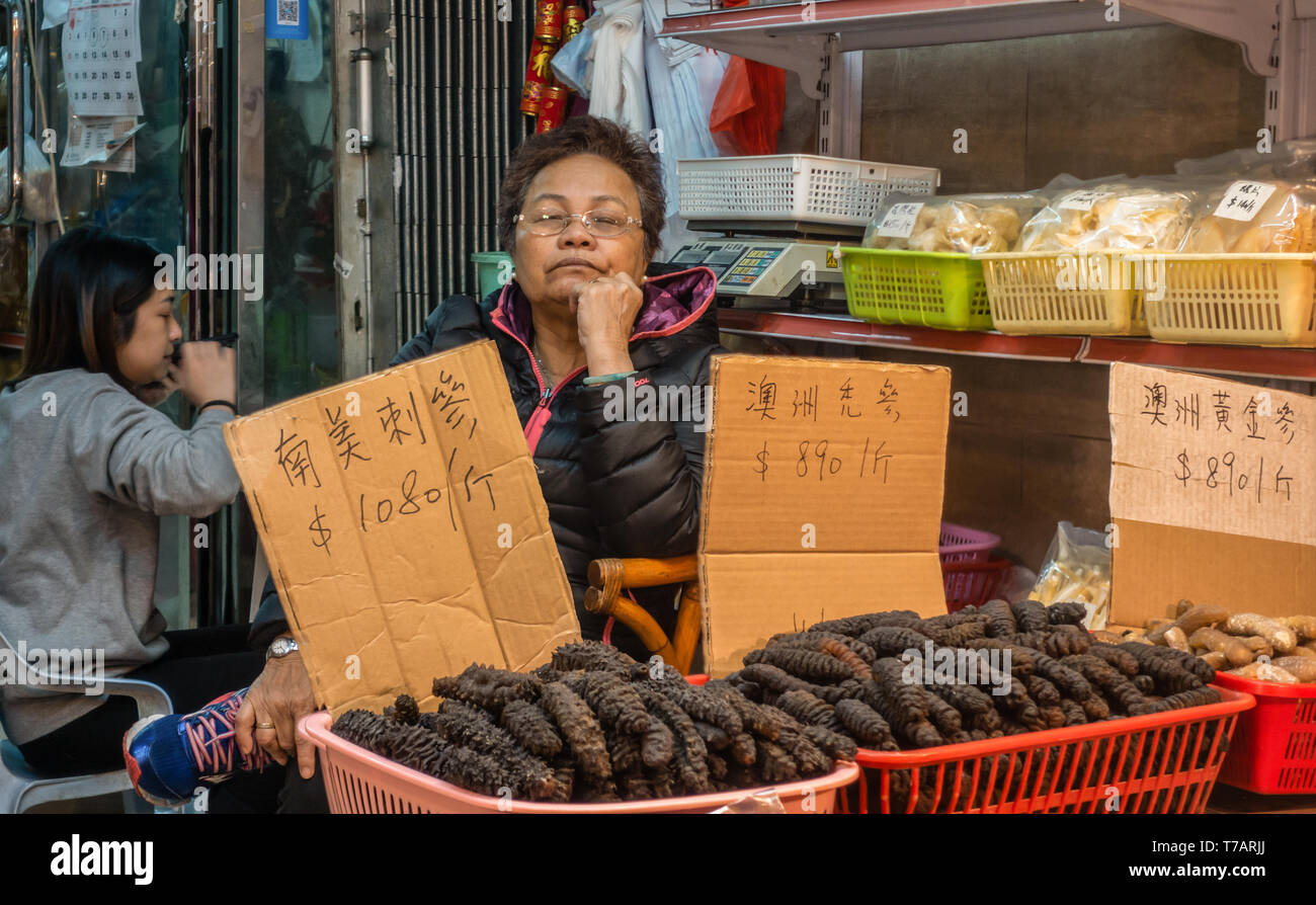 Hong Kong, China - March 7, 2019: Tai O Fishing village. Sleeping lady sells blackish sea cucumbers out of red baskets in a store front. Scale and gir - Stock Image
