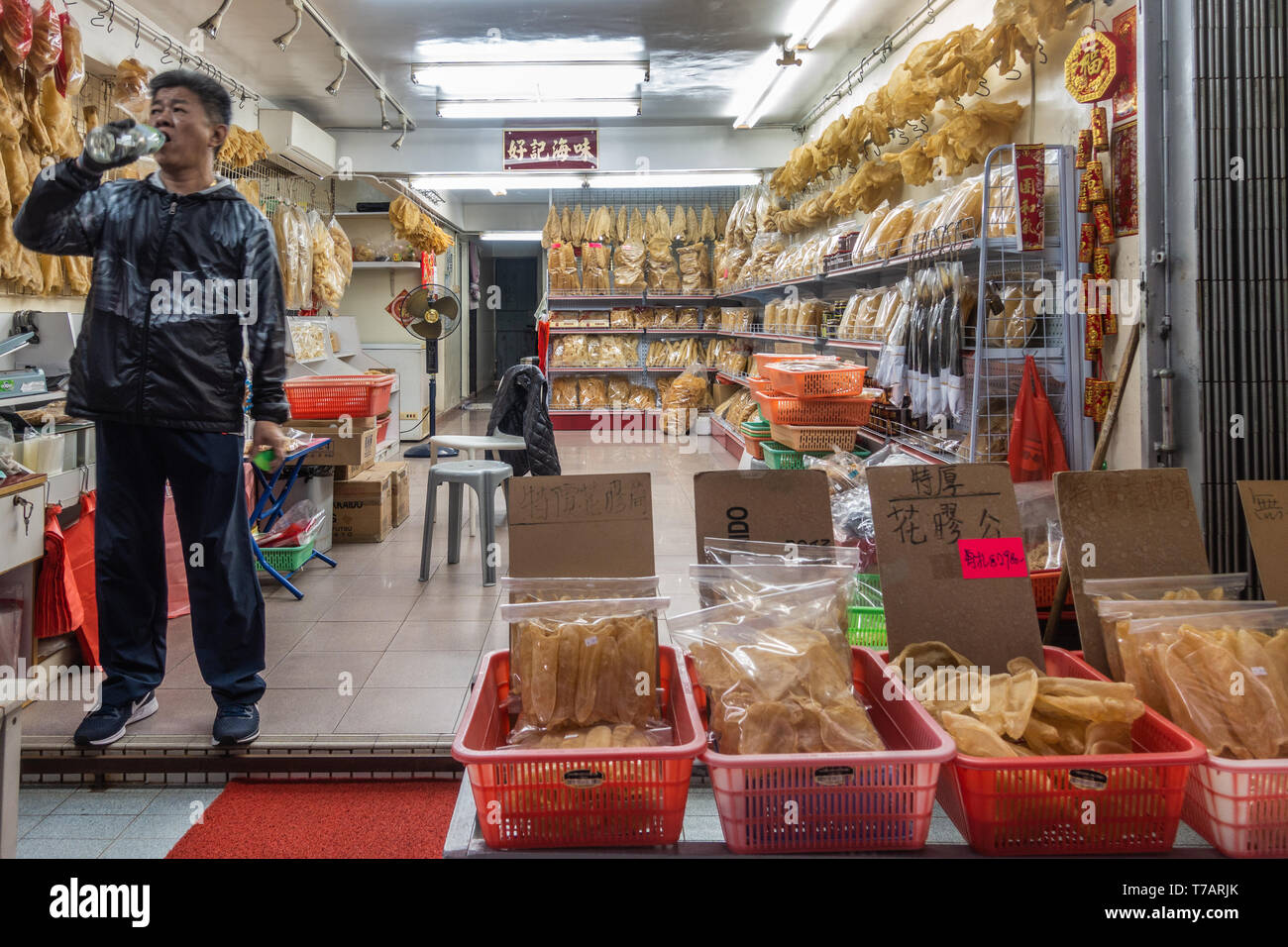 Hong Kong, China - March 7, 2019: Tai O Fishing village. Shop owner is black clothes drinks water while guarding his large dried seafood store, disply - Stock Image