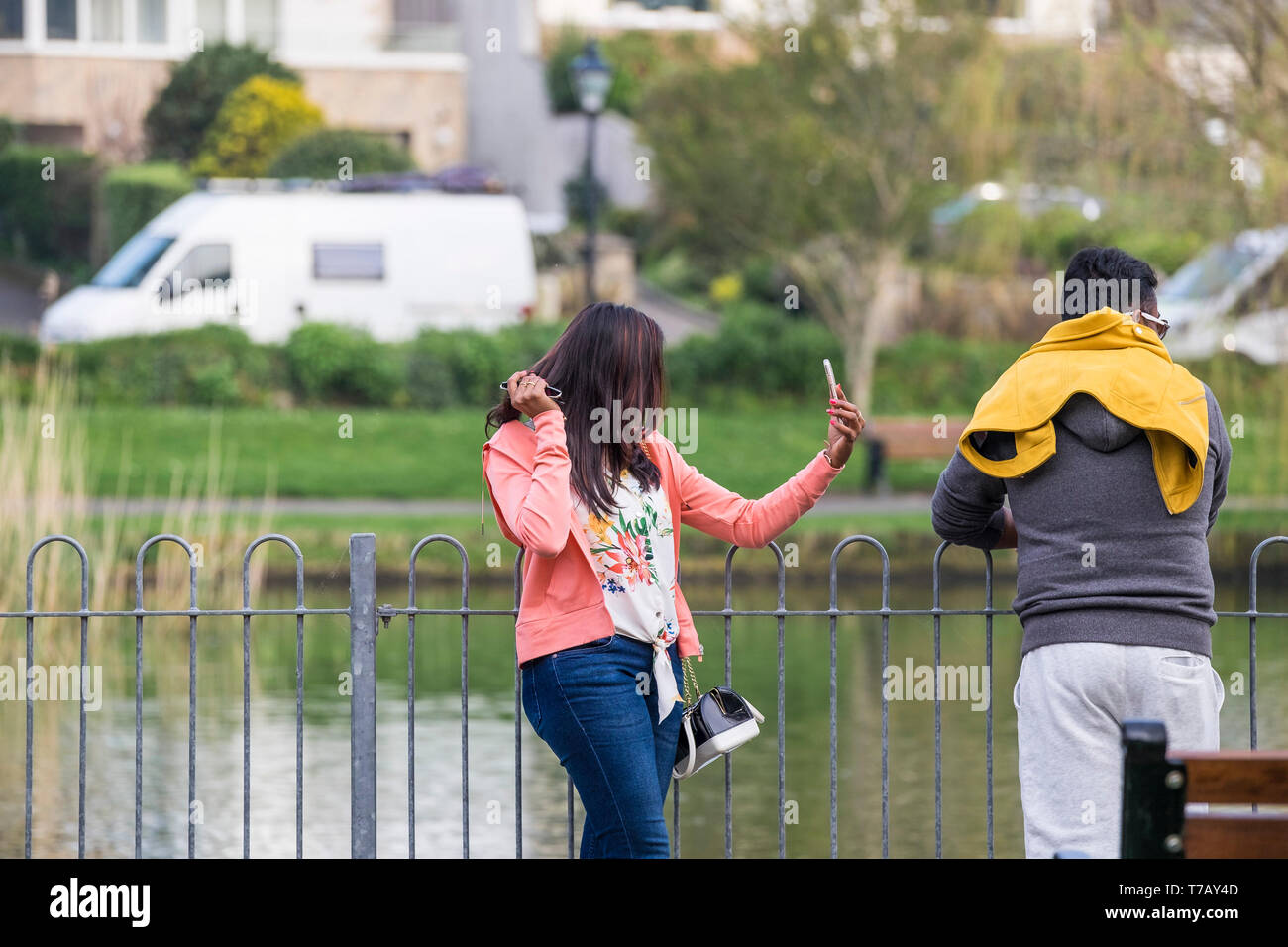 A narcissistic woman taking a selfie with her smartphone as her disinterested boyfriend ignores her. - Stock Image