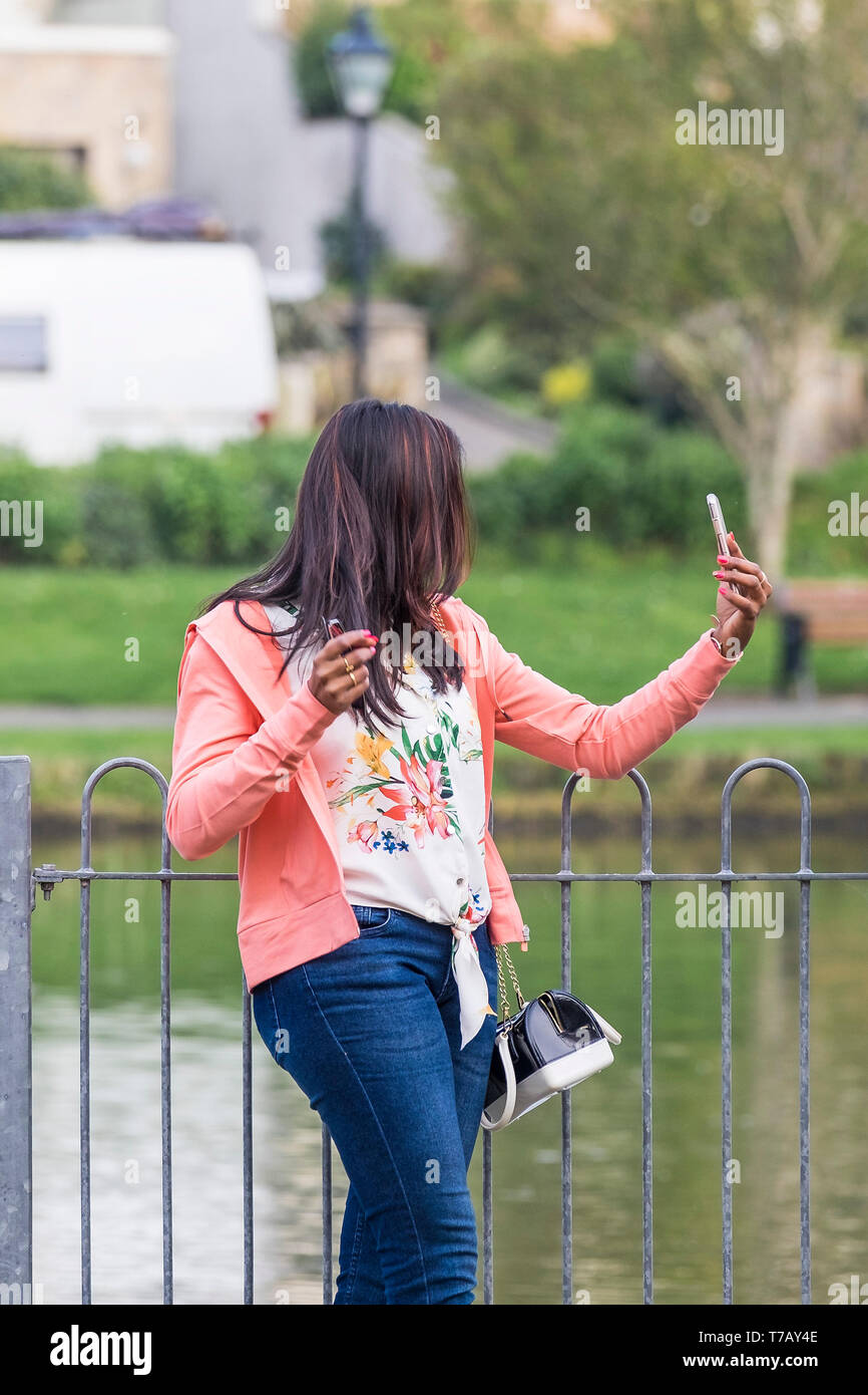 A narcissistic woman taking a selfie with her smartphone. - Stock Image