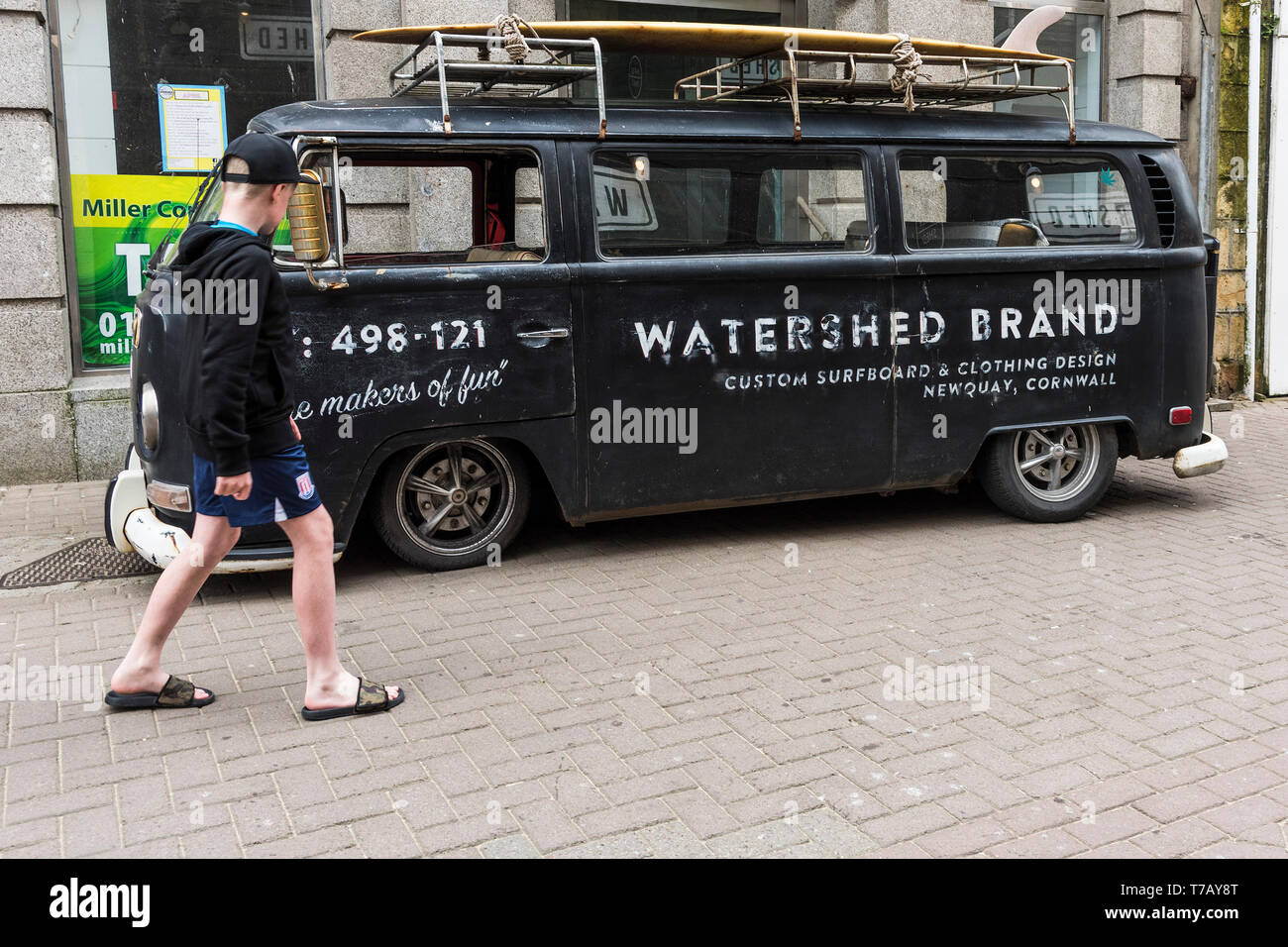 A young holidaymaker admires a vintage rat look Volkswagen campervan advertising Watershed Brand parked in Newquay Town Centre in Cornwall. - Stock Image