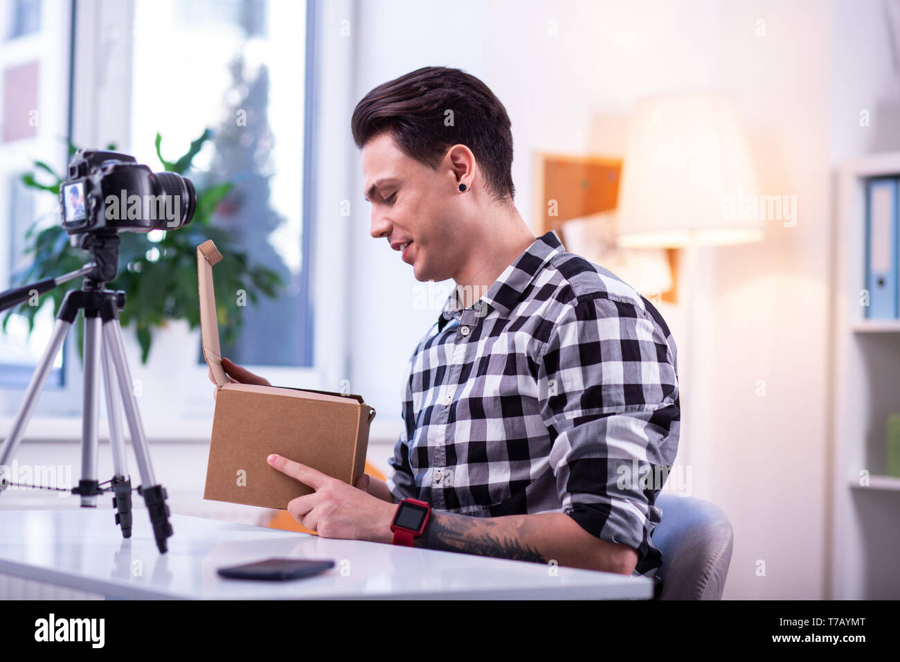 Curious short-haired stylish guy opening box with new product - Stock Image