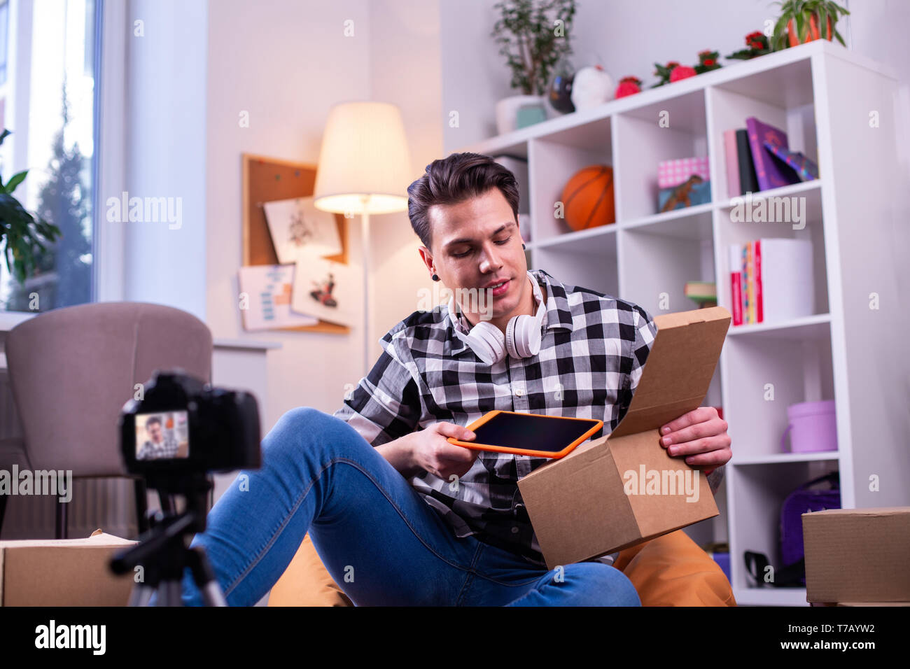 Inspired handsome man making review of new generation of electronic tablet - Stock Image