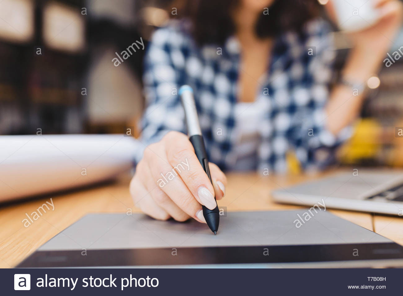 Closeup image hand of woman designing on table in library surround work stuff. Laptop, creative work, graphic design, freelancer, smart student, love job Stock Photo