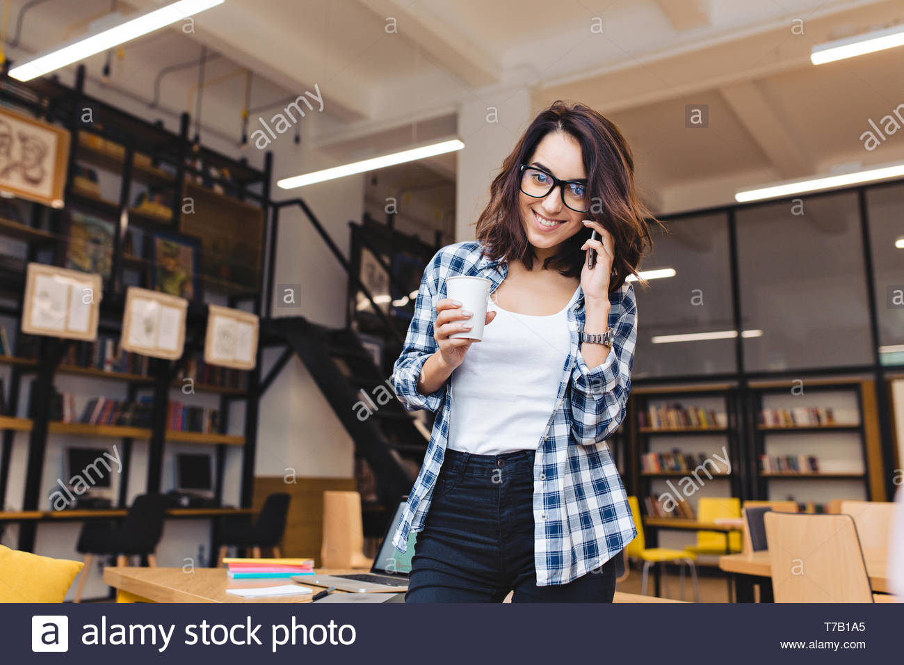 Attractive young brunette woman with coffee talking on phone and smiling to camera in library. Coffee-break, university life, modern work, studying, smart student, good job Stock Photo