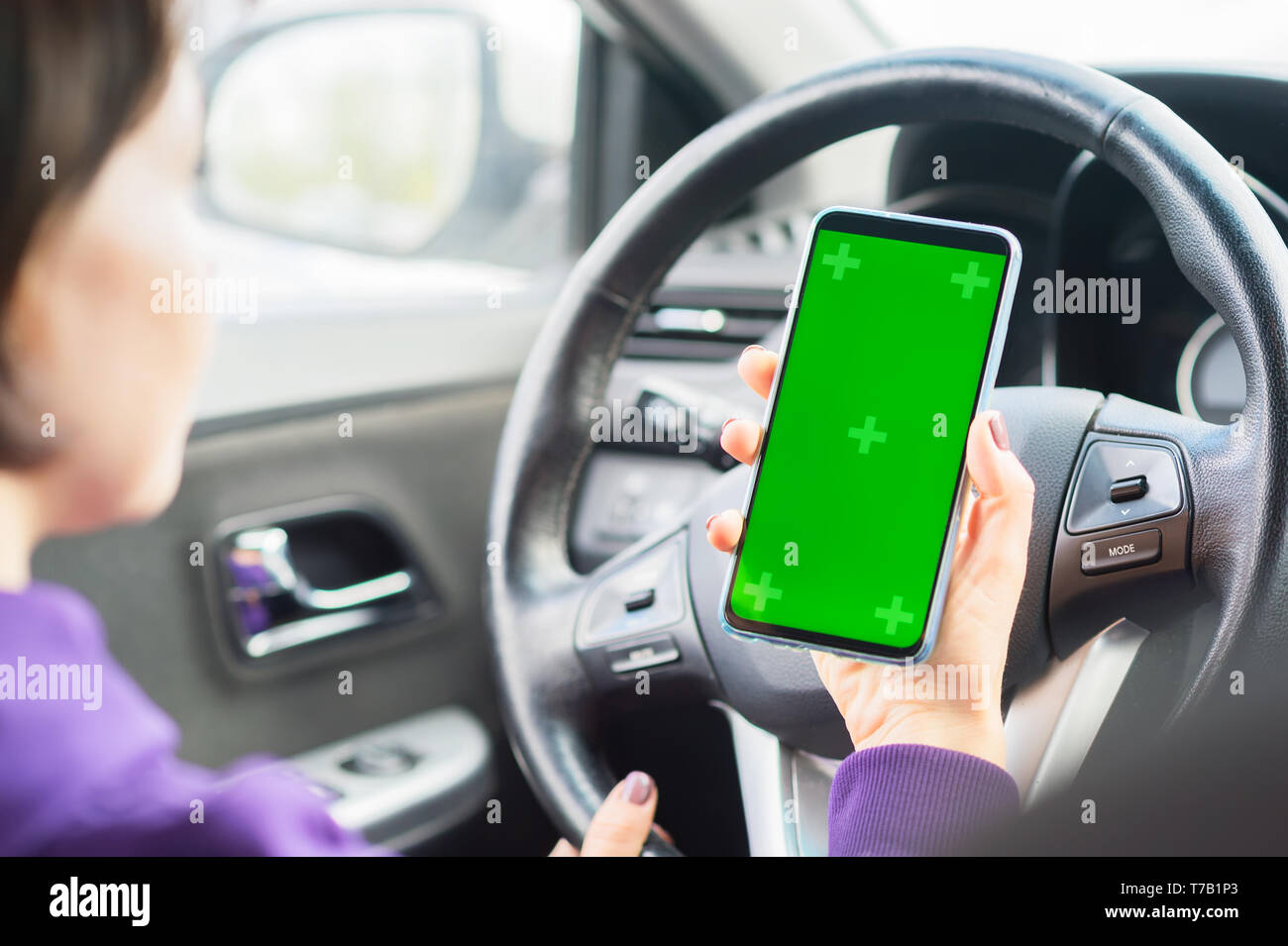 Young female driver using touch screen smartphone in a car. green chroma key on the phone display. - Stock Image