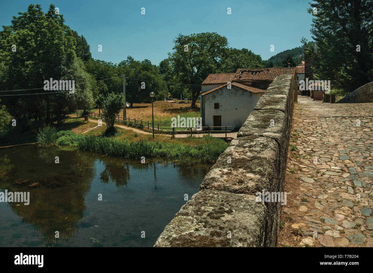 Pavement and parapet on an old Roman bridge still in use over the Sever River at Portagem. A district of Marvão at the bottom valley in Portugal. - Stock Image