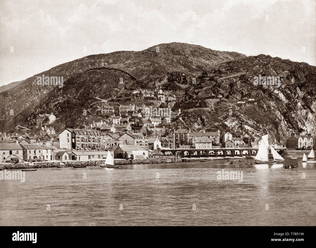 A late 19th Century view of Barmouth, a town in the county of Gwynedd, north-western Wales, lying on the estuary of the River Mawddach and Cardigan Bay. The town grew around the shipbuilding industry, and more recently as a seaside resort. William Wordsworth, a visitor to Barmouth in the 19th century, described it thus: 'With a fine sea view in front, the mountains behind, the glorious estuary running eight miles inland, and Cadair Idris within compass of a day's walk, Barmouth can always hold its own against any rival.' - Stock Image
