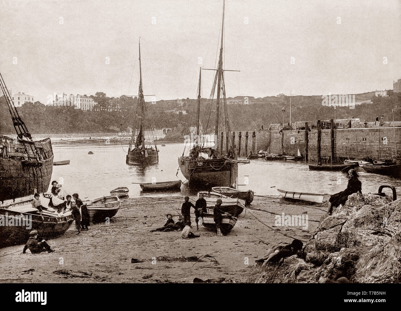 A late 19th Century view of  the harbour at Tenby, a walled seaside town in Pembrokeshire, Wales, on the western side of Carmarthen Bay. The town's fortunes rose when a local resident, merchant banker and politician, Sir William Paxton invested heavily in the area. With the growth in saltwater sea-bathing for health purposes, Paxton went on to create a 'fashionable bathing establishment suitable for the highest society. - Stock Image