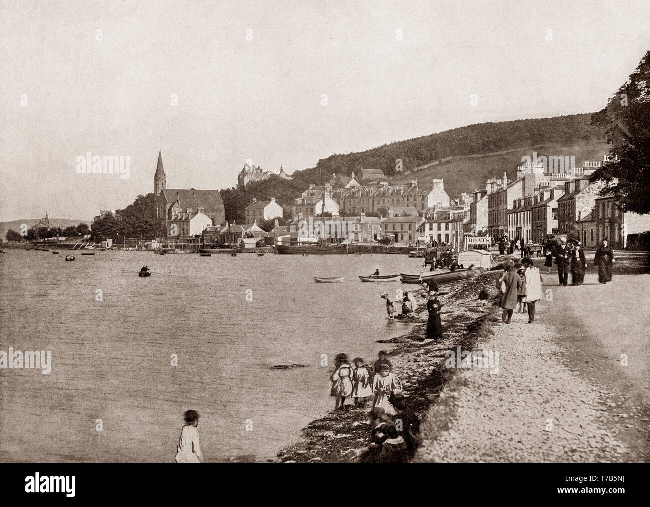 A late 19th Century view of the seafront at Port Bannatyne on the Isle of Bute, Firth of Clyde, Scotland. The village started in 1801 with the building of a small harbour on Kames Bay. Lord Bannatyne of Kames Castle, at the head of the bay, planned the village in an attempt to rival Rothesay. Initially known as Kamesburgh, by the mid-19th century, steamers were calling there regularly. In 1860 the Marquess of Bute purchased this part of the island and renamed the village Port Bannatyne in honour of the long historical association of the Bannatyne family with the area. - Stock Image