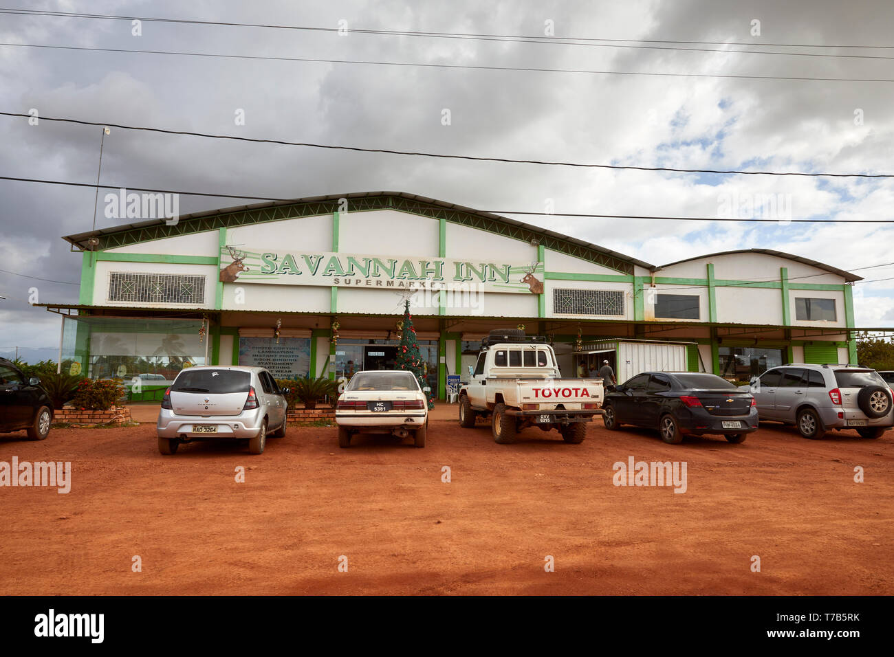 Cars parked in front of Savannah Inn Supermarket on Rupununi Road in Lethem Guyana South America - Stock Image