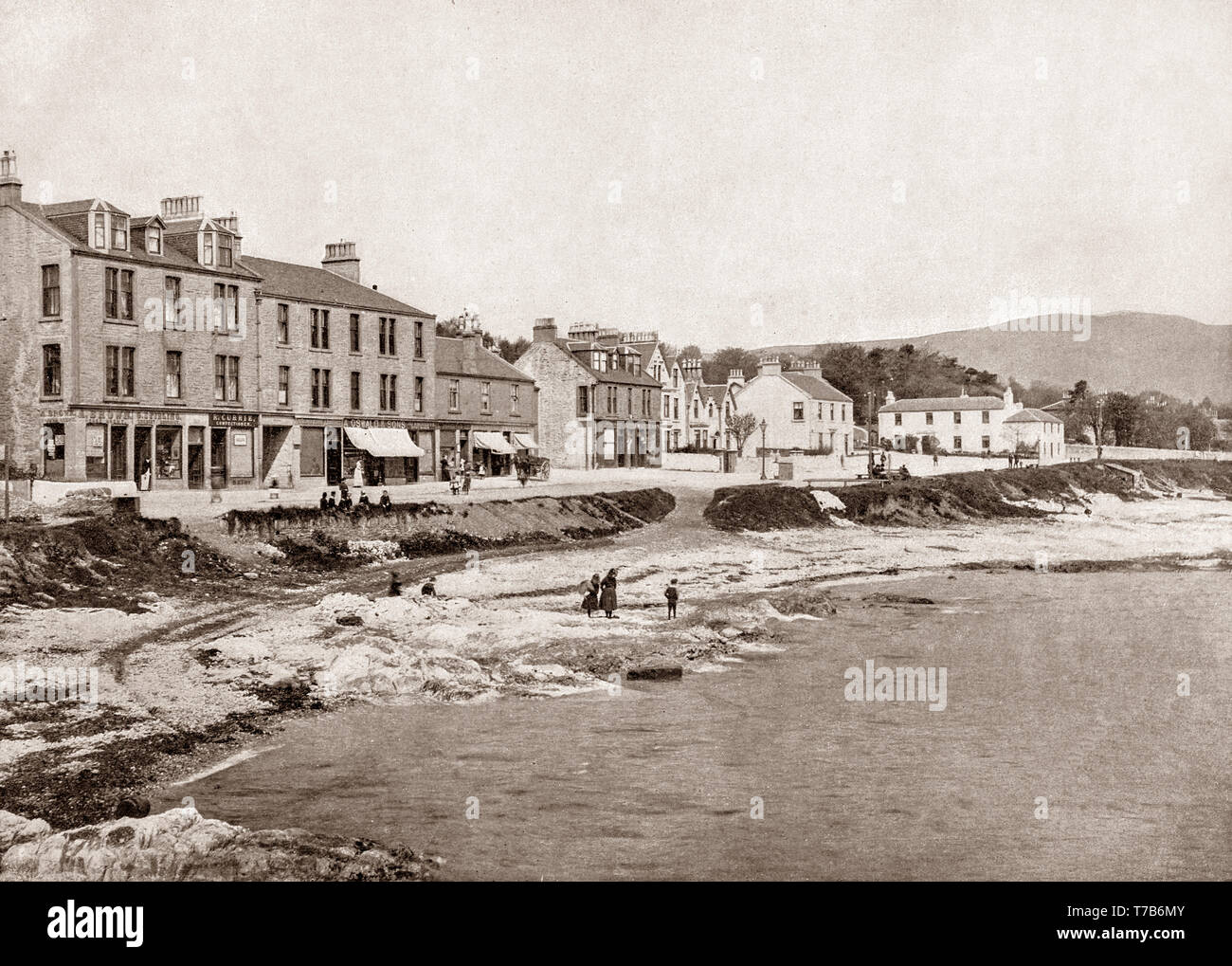 A late 19th Century view of the seafront of Kirn, a village in Argyll and Bute in the Scottish Highlands on the west shore of the Firth of Clyde on the Cowal peninsula. This photograph was shot from the landing stage, a regular stop for the Clyde steamer services, bringing holidaymakers  from the Glasgow area to the town. - Stock Image