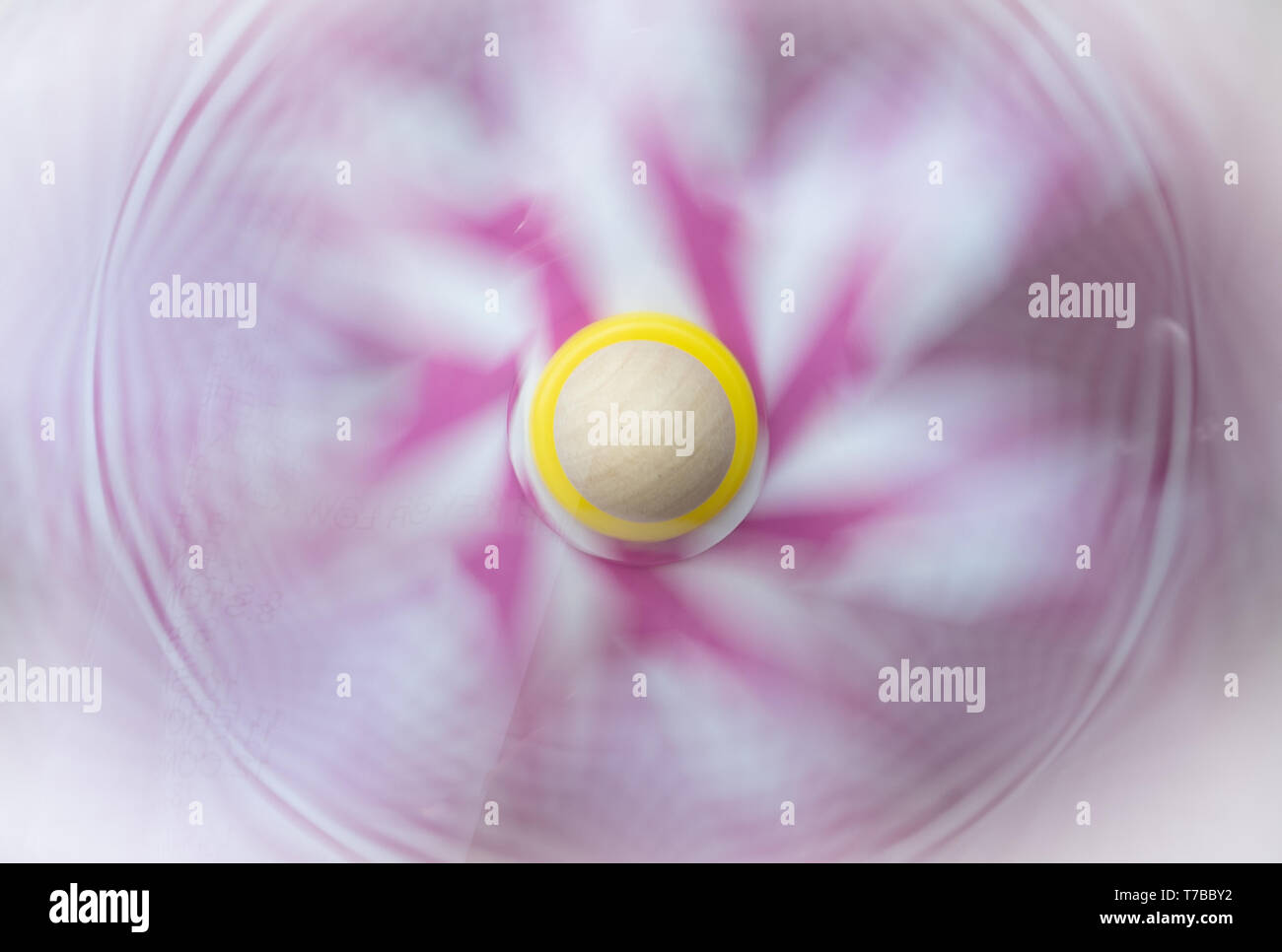 Close up of a spinning pink and white pinwheel with a wooden center. - Stock Image