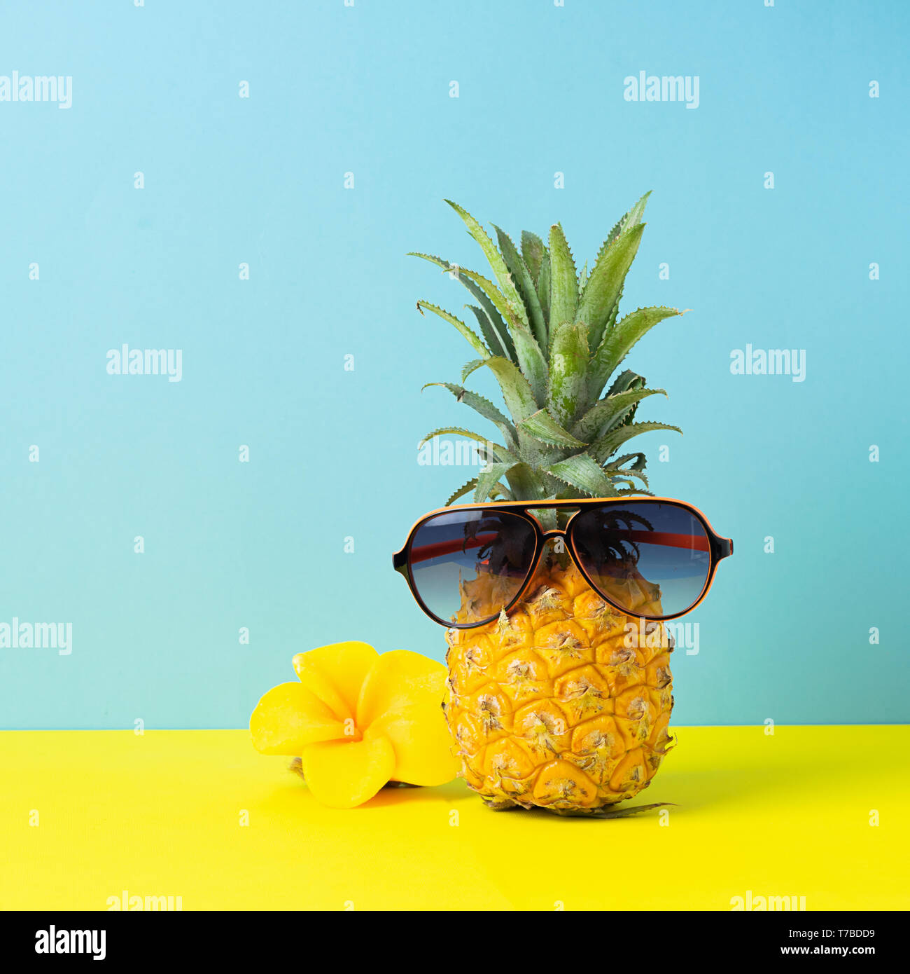 1a7091bf6f6a Yellow ripe pineapple in sunglasses on a yellow blue background. Funny face  from a tropical