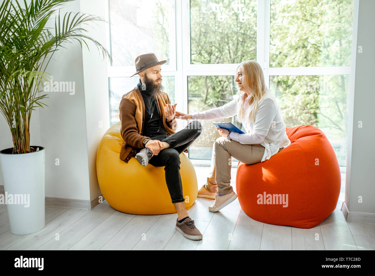 Stylish Man With Senior Female Psychologist Or Mental Coach Sitting On The  Comfortable Chairs During The Psychological Counseling In The Office