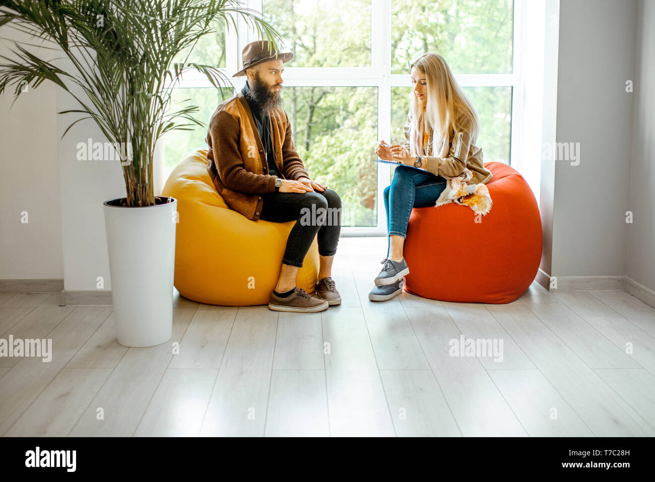 Young Man And Woman Sitting On The Comfortable Chairs During The  Psychological Counseling, Solving Some Psychological Problems In The Office