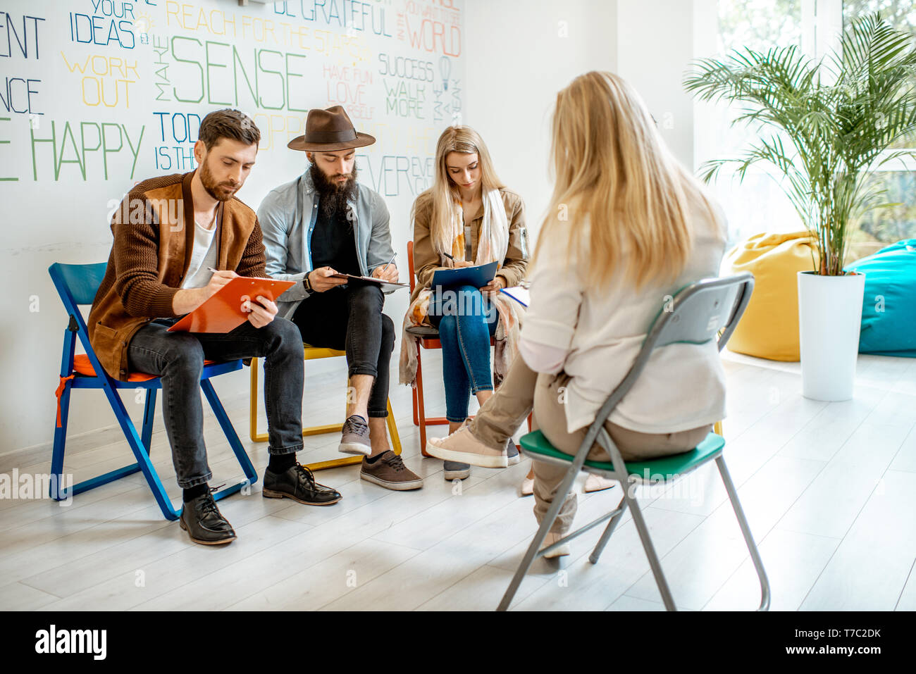 Group of young people sitting together during the psychological therapy with psychologist solving some mental problems in the office Stock Photo