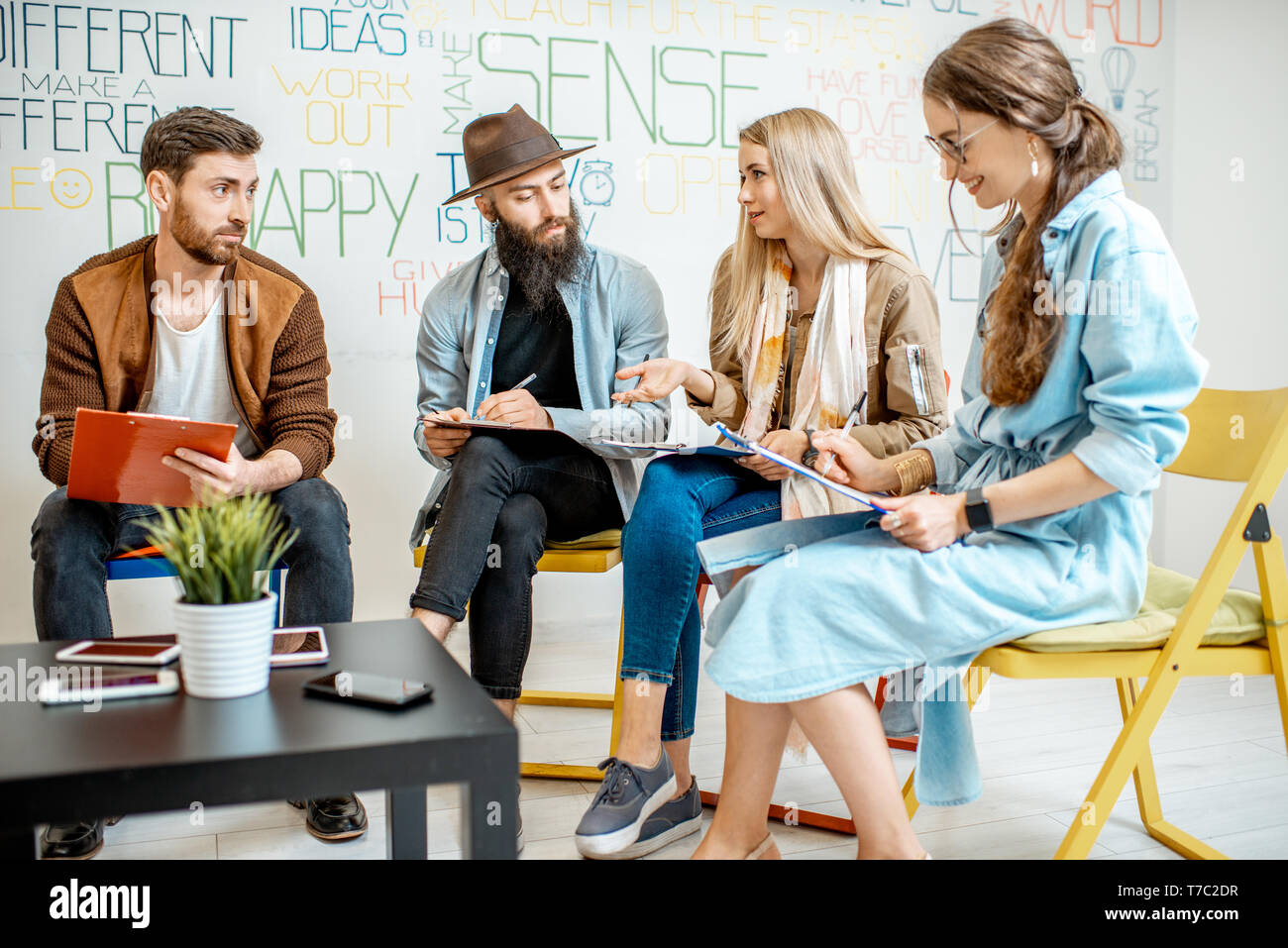 Group of people variously dressed writing some mental test during the psychological training, sitting together in the office Stock Photo