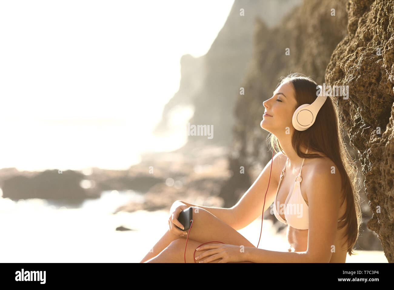 Side view portrait relaxed sunbather listening to music with smart phone and headphones on the beach - Stock Image