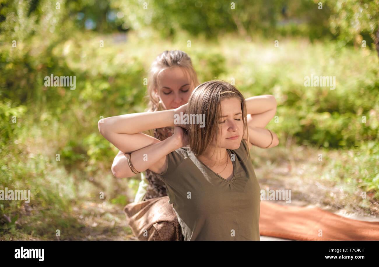 Experienced masseuse demonstrates refreshing massaging methods in nature. - Stock Image