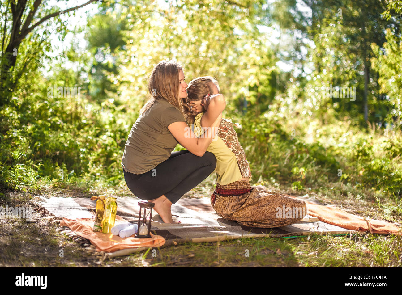 Girl masseuse provides a thorough massage  in the daylight. - Stock Image