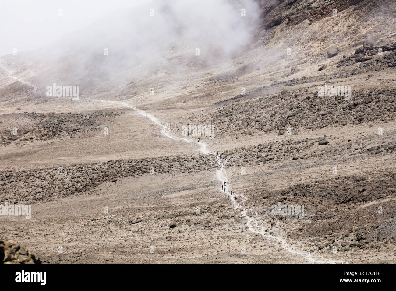 Thin road in a mountains leads to the top. Sand and stones on the ground, dry land. Clouds up on the sky. Travelling in a desert of Africa. Sunny hot Stock Photo