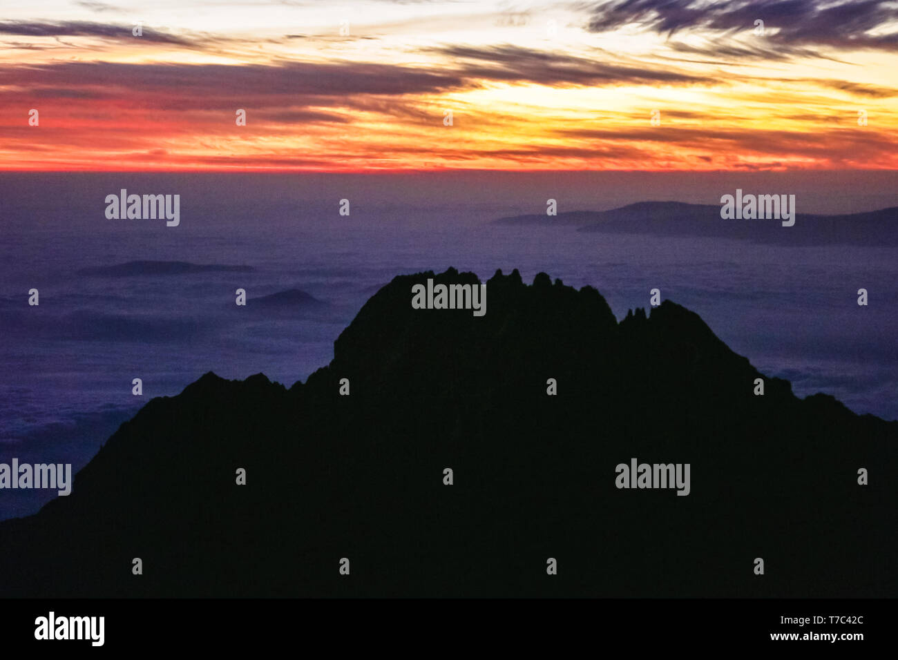 Orange sun is rising on the horizon, light falling on the clouds near the mountain peaks. Black sharp rocks. Adventures and trip in Africa. Stock Photo