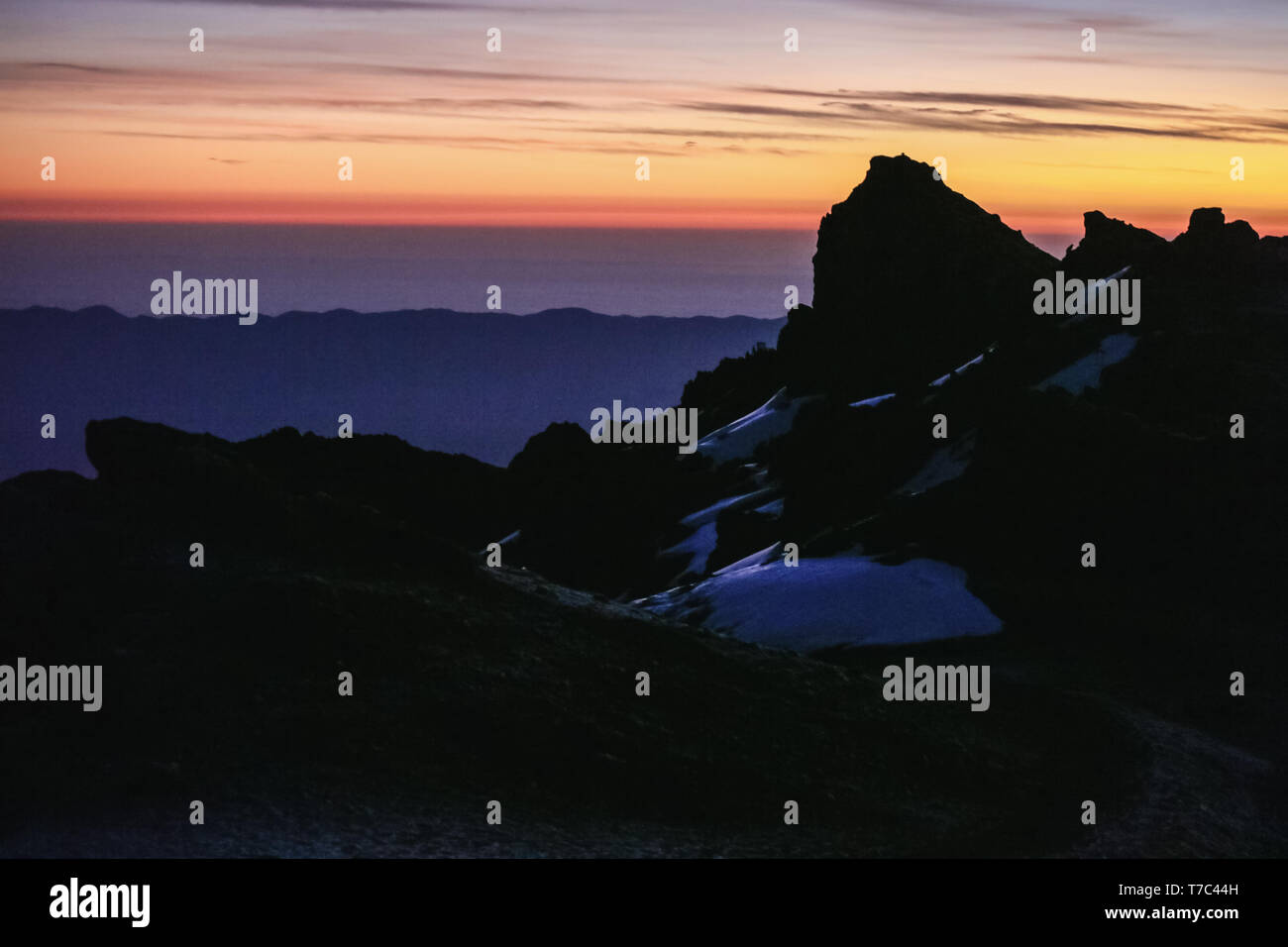 Incredible morning landscape of the rocks on colorful sky background. Black hills covered with snow.Beautiful sunrise on Kilimanjaro, extreme and cool Stock Photo