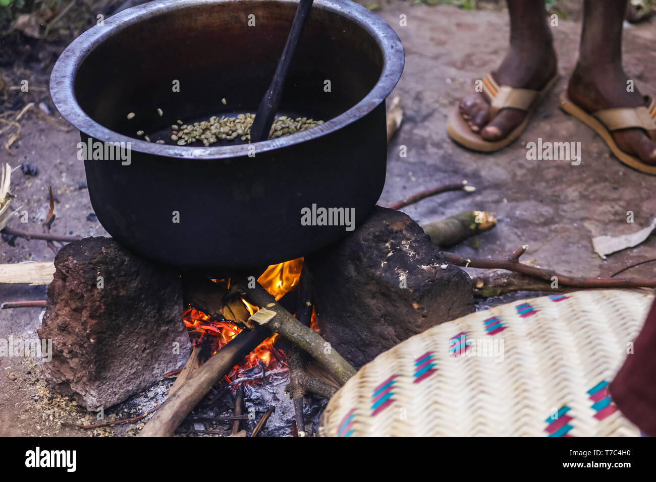 Traditional african morning near the bonfire with fresh roasted aromatic cup of coffee. Big deep pot with green coffee beans on the open fire. Stock Photo