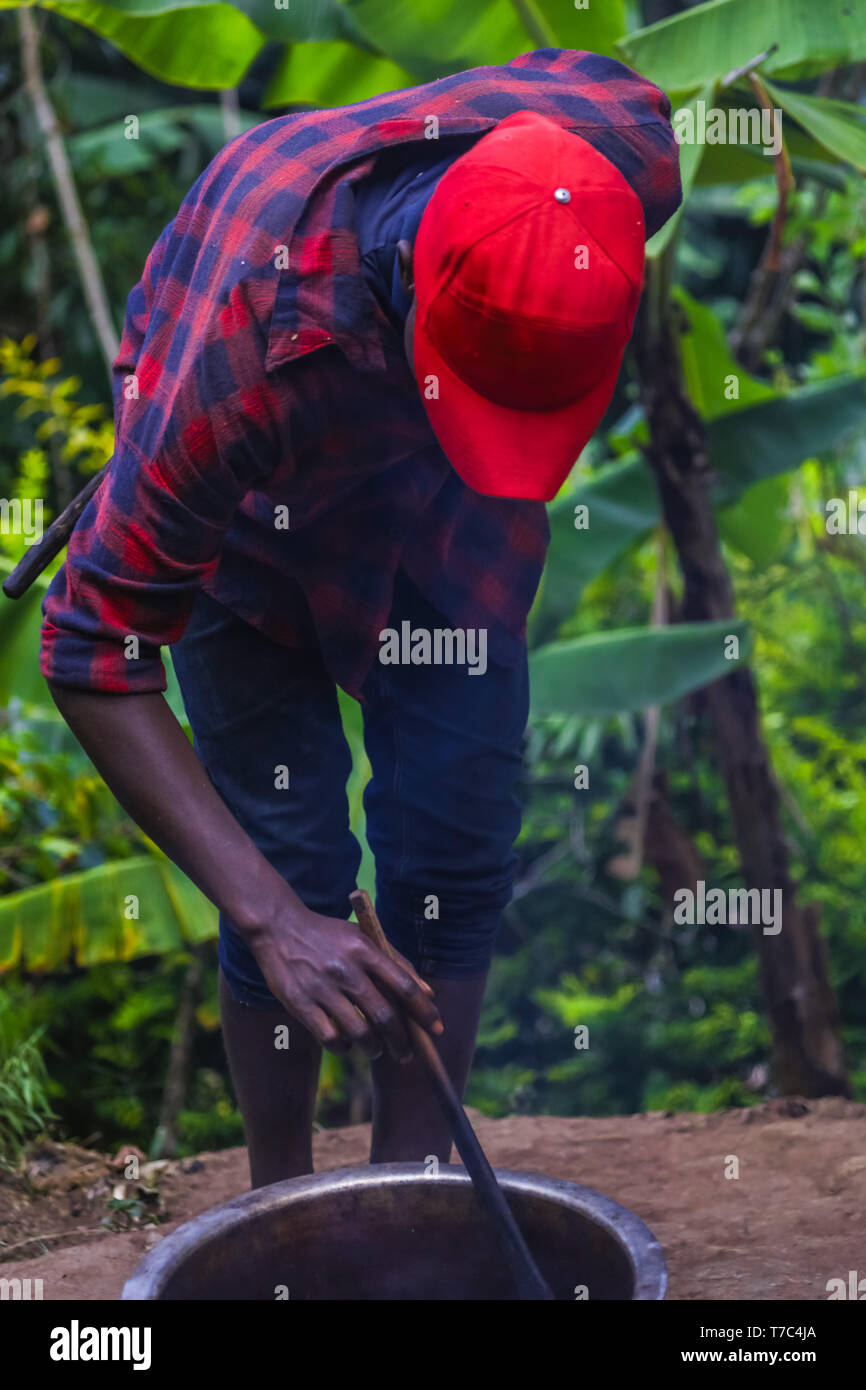 Black guy cooking outdoor on the bonfire.Big metal pot, making morning tasty coffee from roasted coffee beans.Wearing checkered shirt, red cap on head - Stock Image