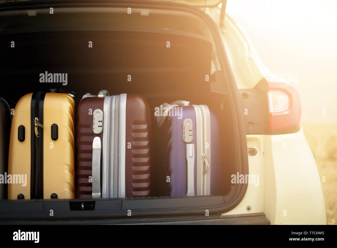 Opened car trunk full of suitcases in sunlight effect. Travel, adventure concept. Packed baggages for summer holidays - Stock Image
