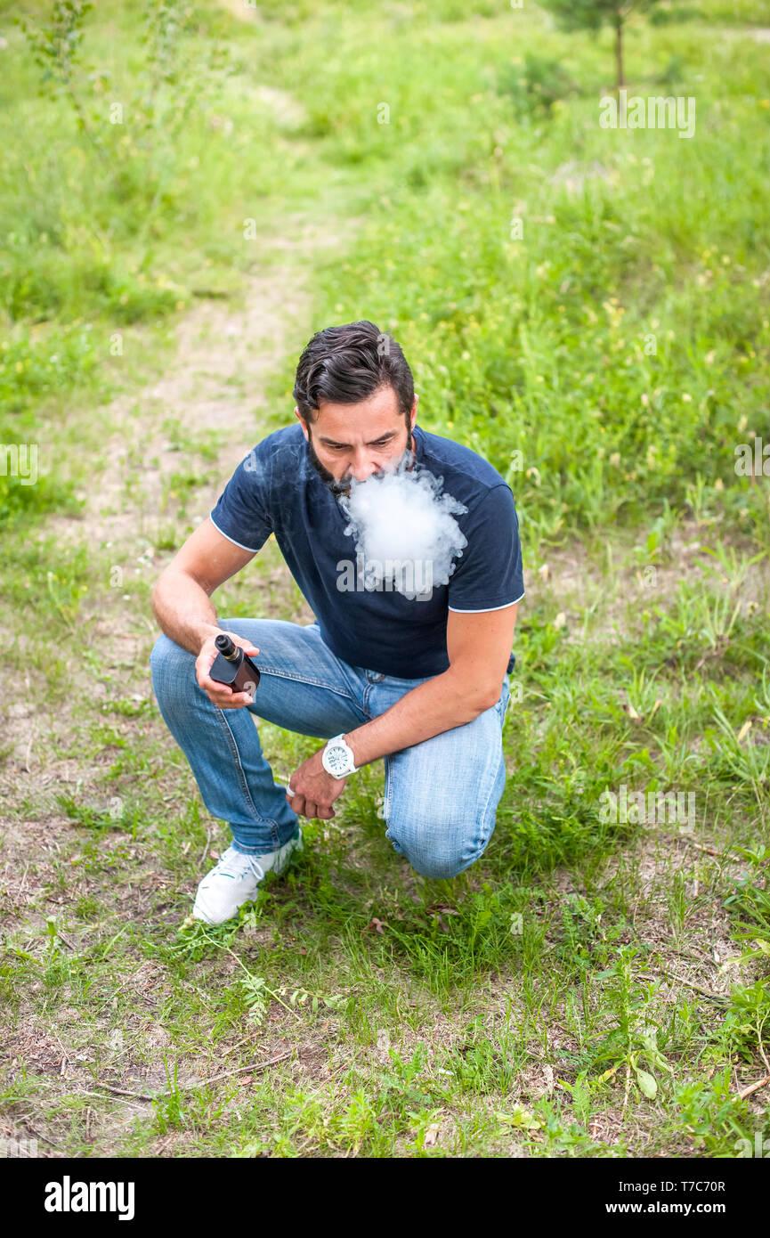 Brutal vaper enjoying e-cigarette in the daylight. Getting rid of nicotine addiction. - Stock Image