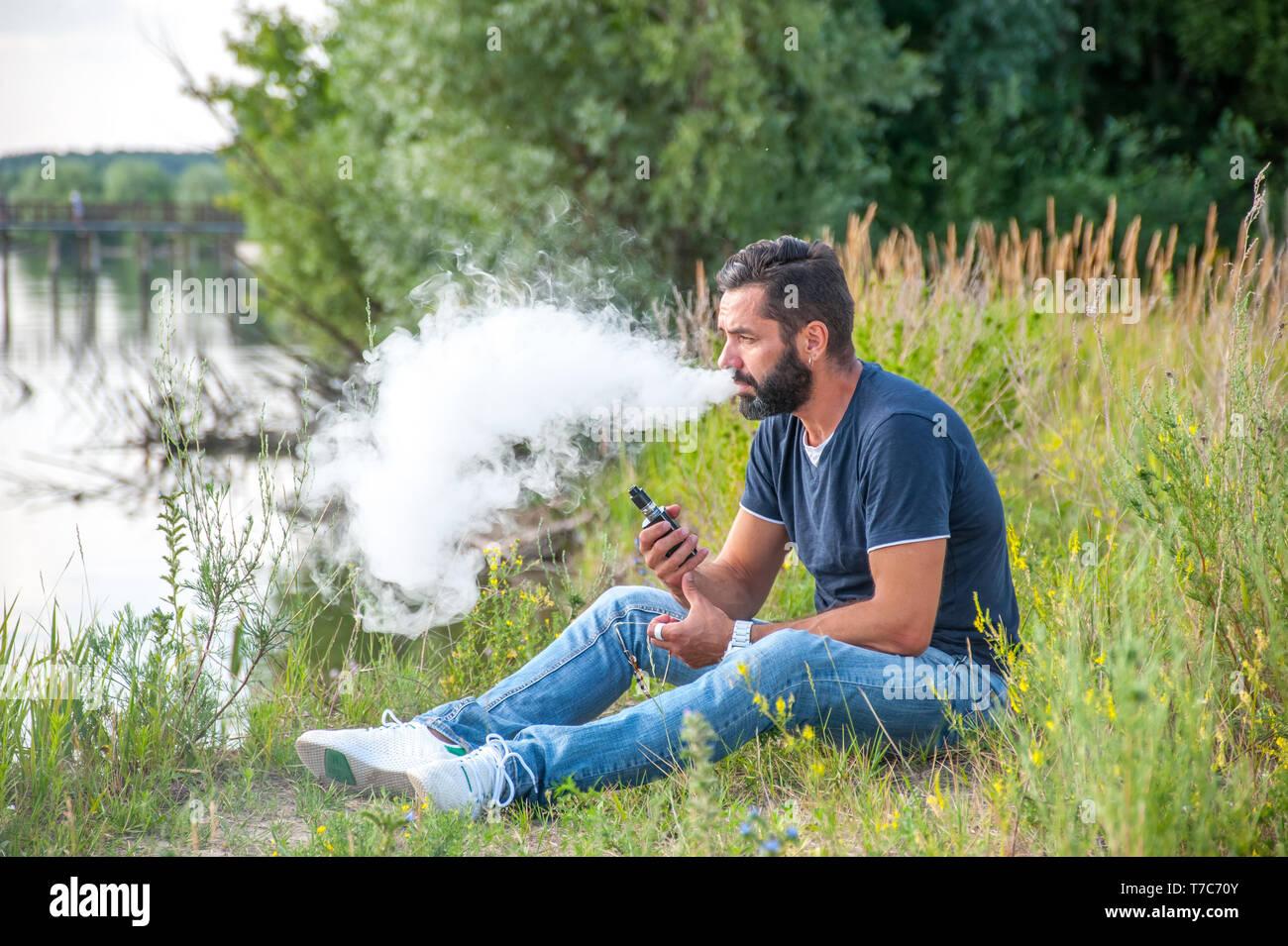 Confident man in the fresh air smoking an electronic cigarette. Electronic cigarette. - Stock Image