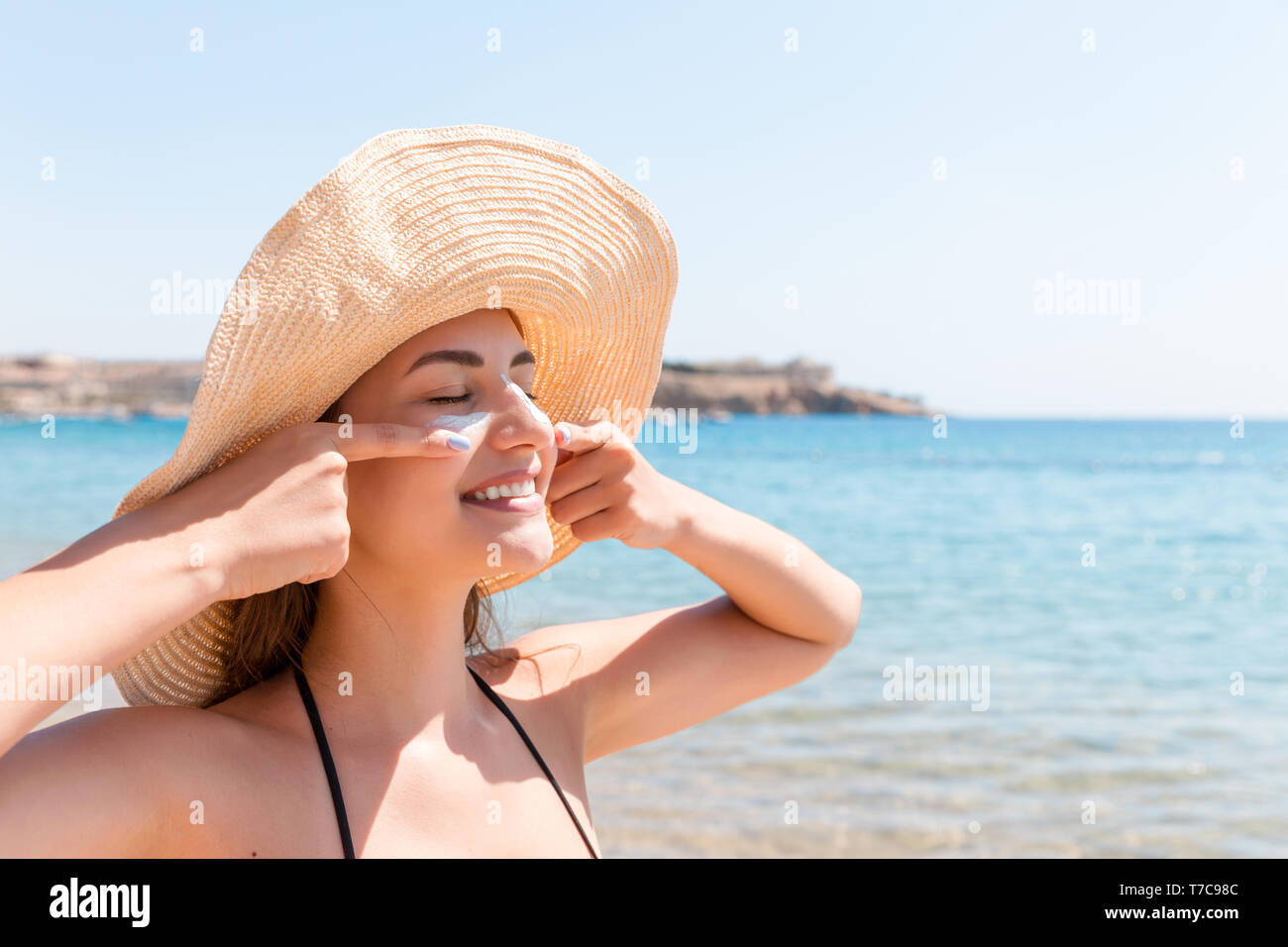 Pretty woman protects her skin on face with sunblock at the beach. - Stock Image