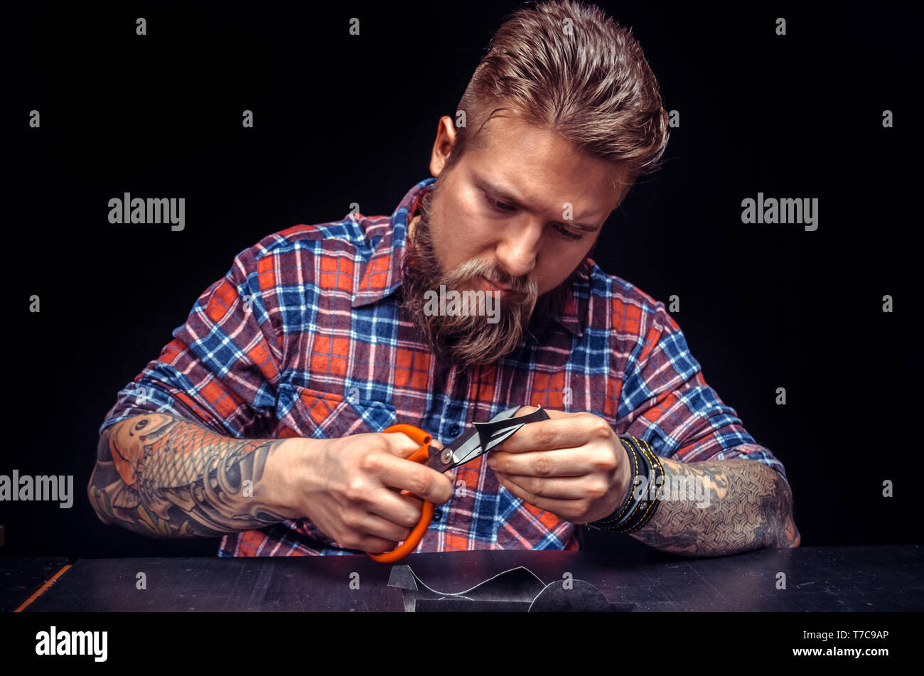 Artisan cutting leather outlines for his new production - Stock Image