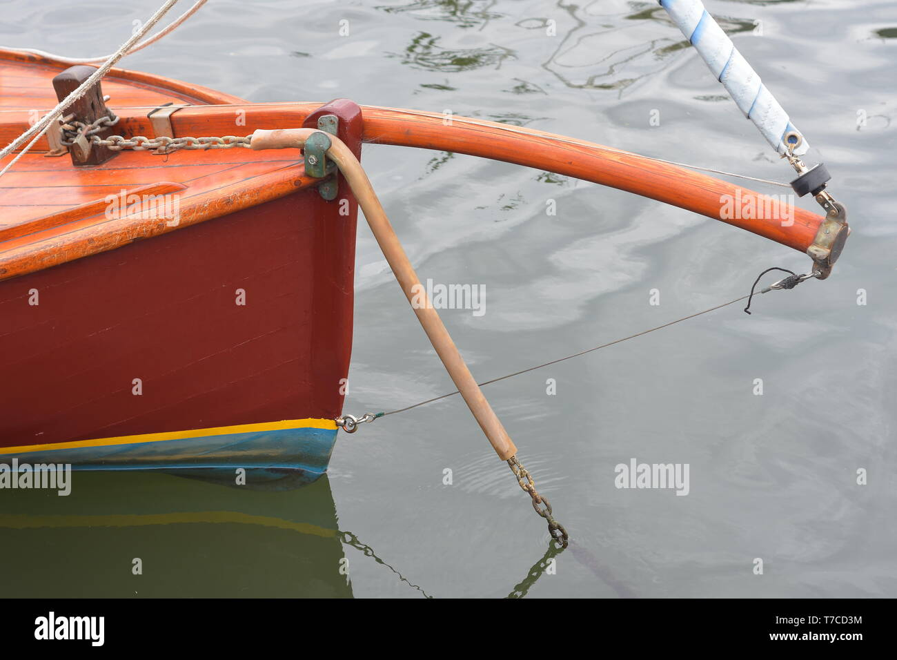 Bow and bent bowsprit with furling headsail of small planked wooden sailing boat on mooring. - Stock Image