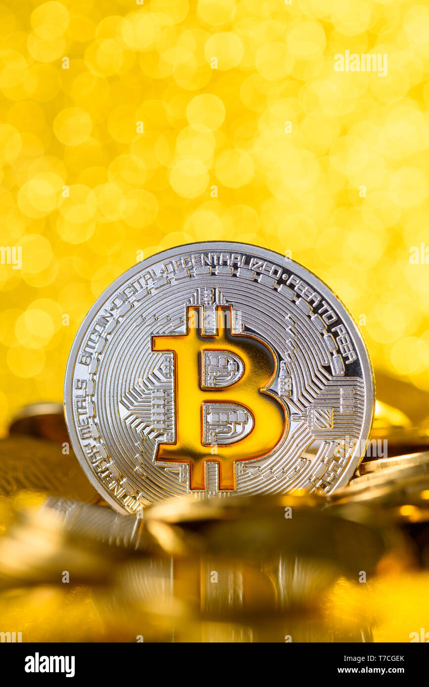 Bitcoin stands on pile of golden coins, big silver coin with gold Bit symbol, vertical with copy space - Stock Image
