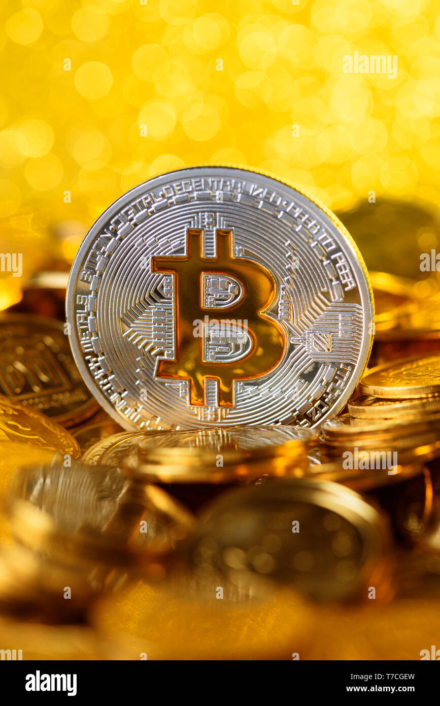 Bitcoin on pile of golden coins, big silver coin with gold Bit symbol, vertical with copy space and shiny lights background - Stock Image